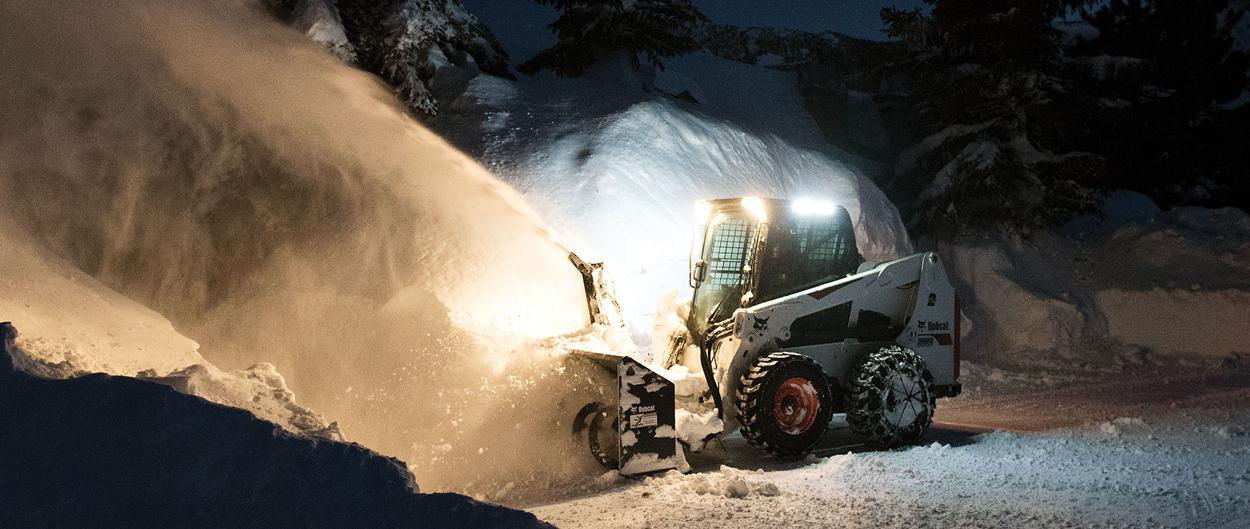 Bobcat S630 skid-steer loader clearing snow with snow blower attachment at night.