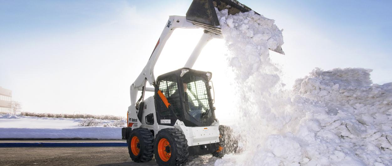 Bobcat S650 skid-steer loader and bucket attachment moving building a snow pile.