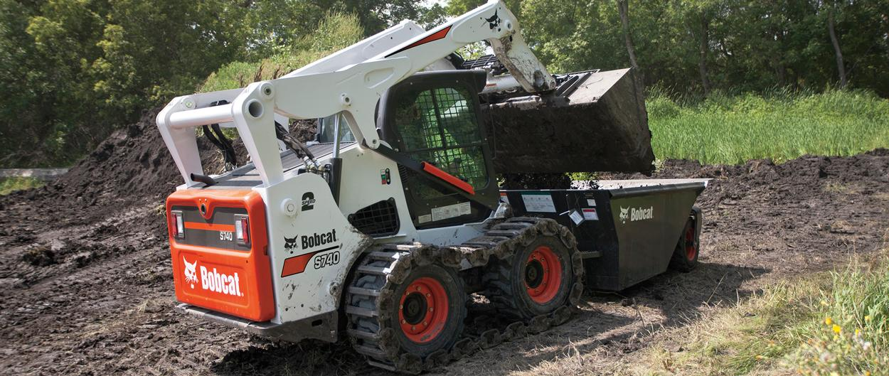 Bobcat S740 skid-steer loader dumping dirt.