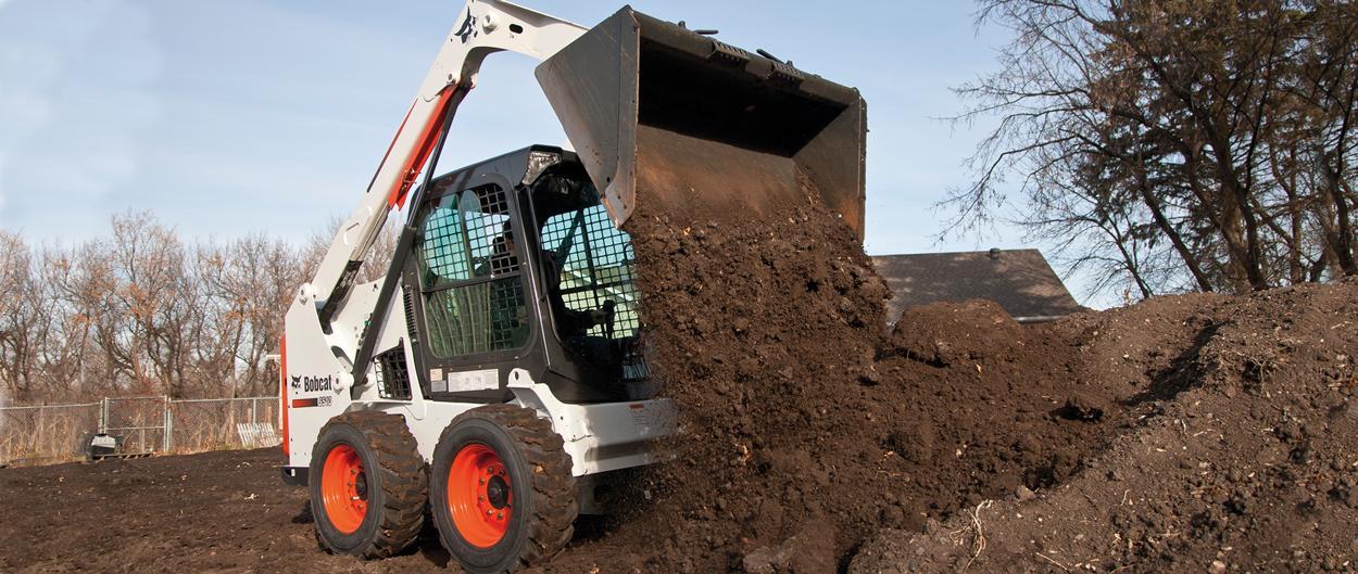 Bobcat S510 skid-steer loader dumps dirt.