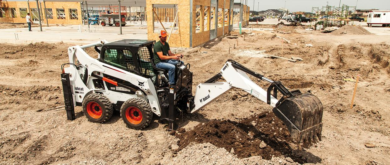 Bobcat S530 skid-steer loader with backhoe attachment on jobsite.