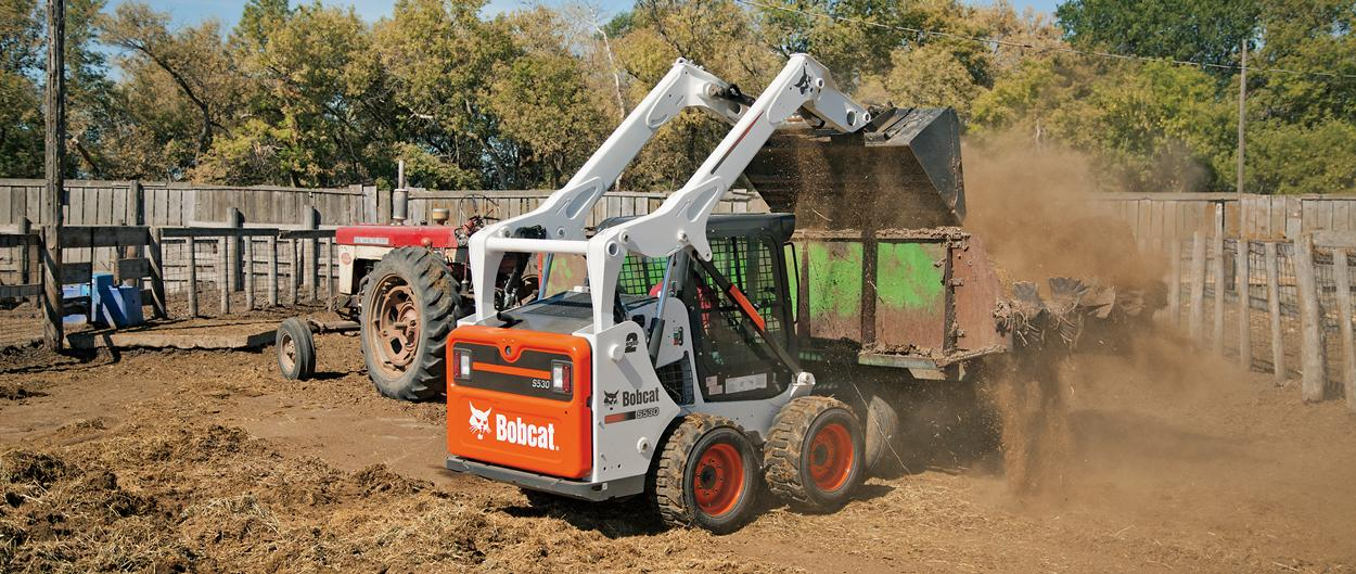 Bobcat S530 skid-steer loader with bucket loads manure.