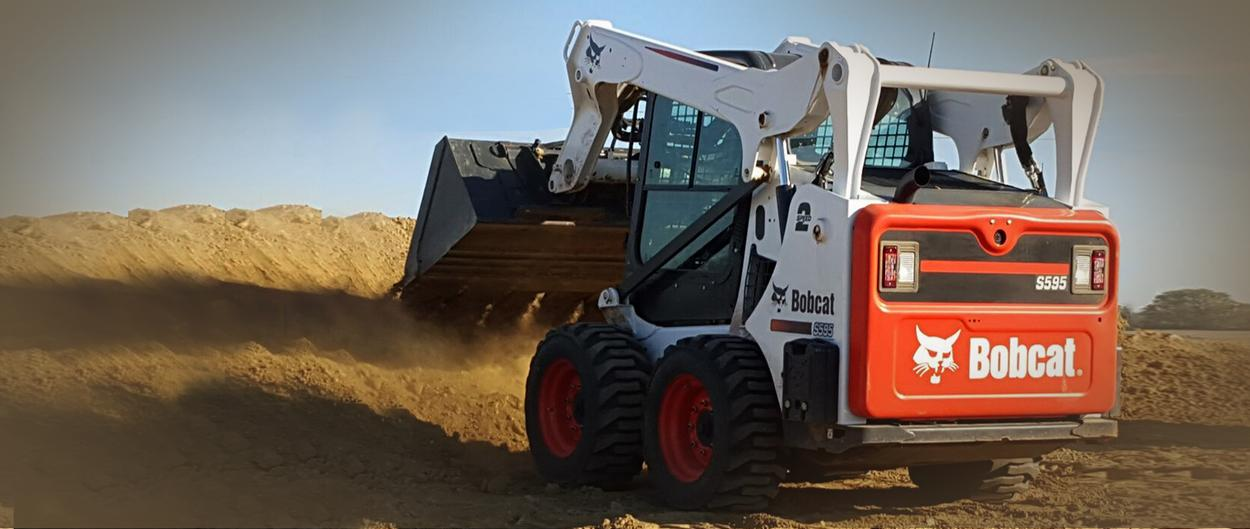 Bobcat S595 skid-steer loader with grapple attachment.