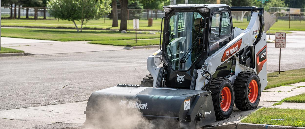 Operator Cleaning Sidewalk With Bobcat S64 Sweeper