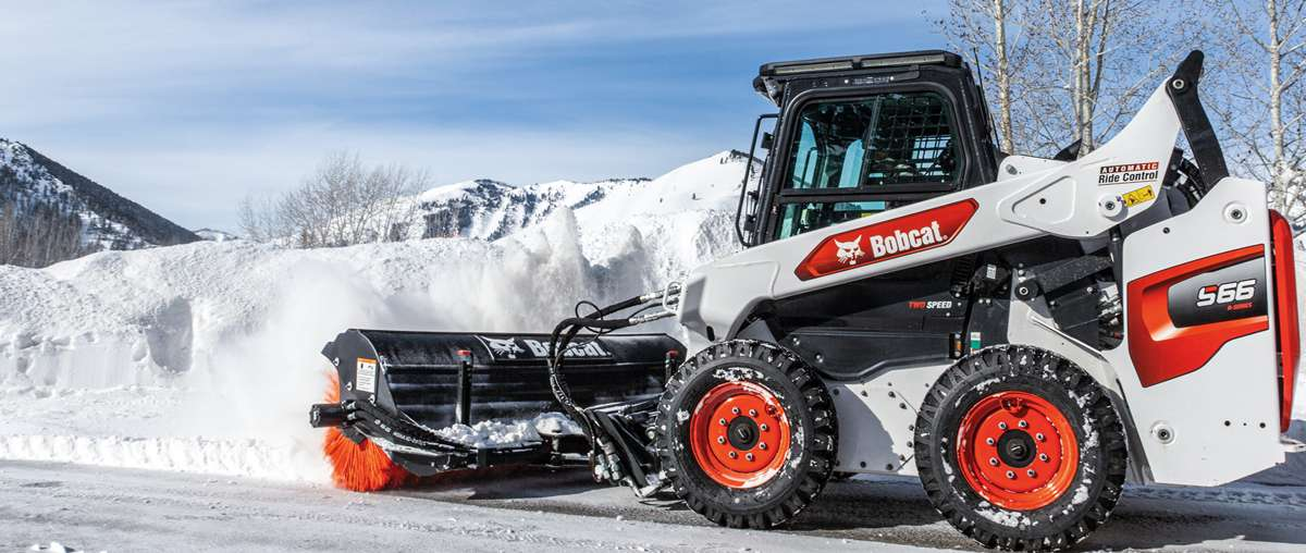 A Bobcat R-Series loader clearing snow with the snow pusher attachment.