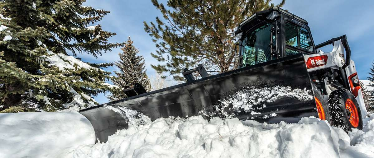 A Bobcat S66 skid-steer loader with snow pusher pro moving snow.