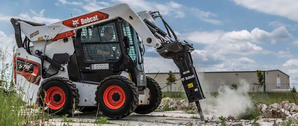 A Bobcat S76 skid-steer loader with nitrogen breaker attachment performing concrete demolition.