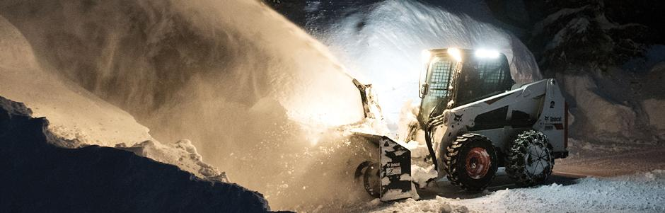 A S630 skid steer loader with a snow blower attachment moves snow.