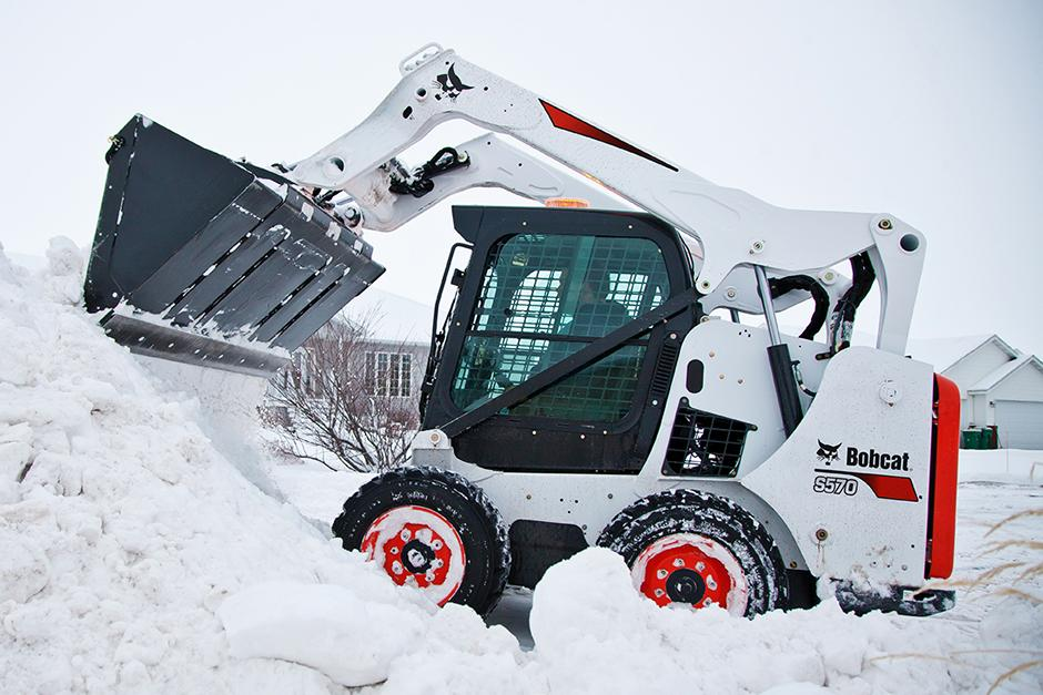 Bobcat S570 skid-steer loader digging in the snow.