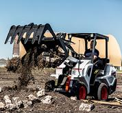 Bobcat Small Articulated Wheel Loader Hauling Material With Grapple Bucket Attachment