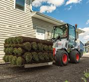Landscaper Using Bobcat Compact Articulated Loader To Haul Sod With Forklift Attachment
