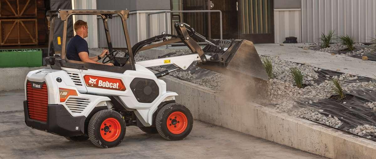 Bobcat Small Articulated Loader Operator Dumps Dirt Into Landscaping Divider