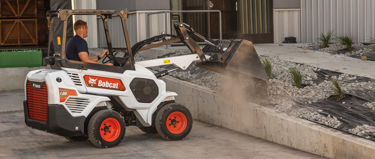 Bobcat Small Articulated Loader Spreading Material Into Landscaping