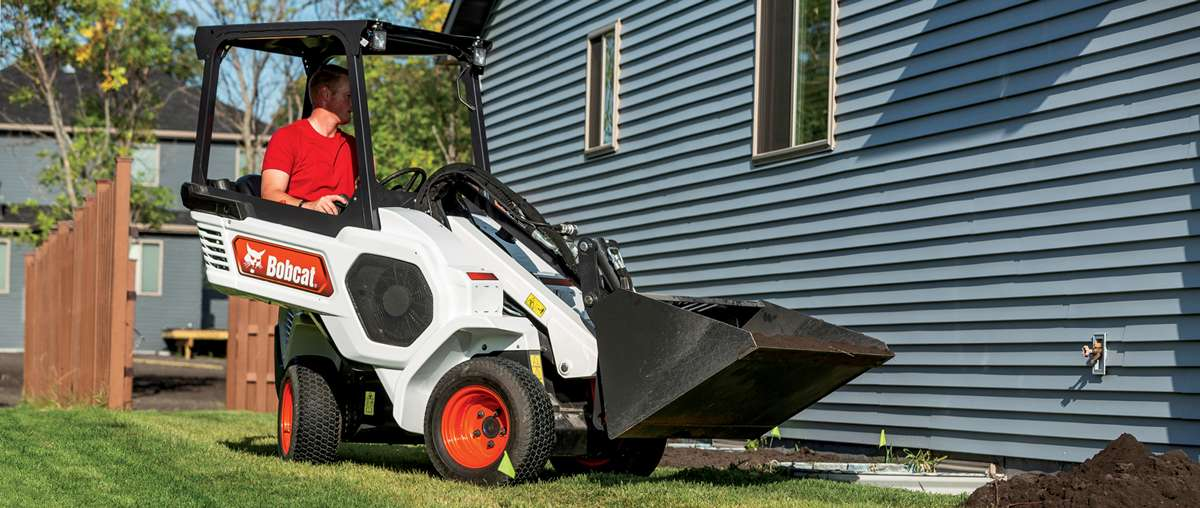 Bobcat Small Articulated Loader Operator Moving Dirt Along The Side Of A House.
