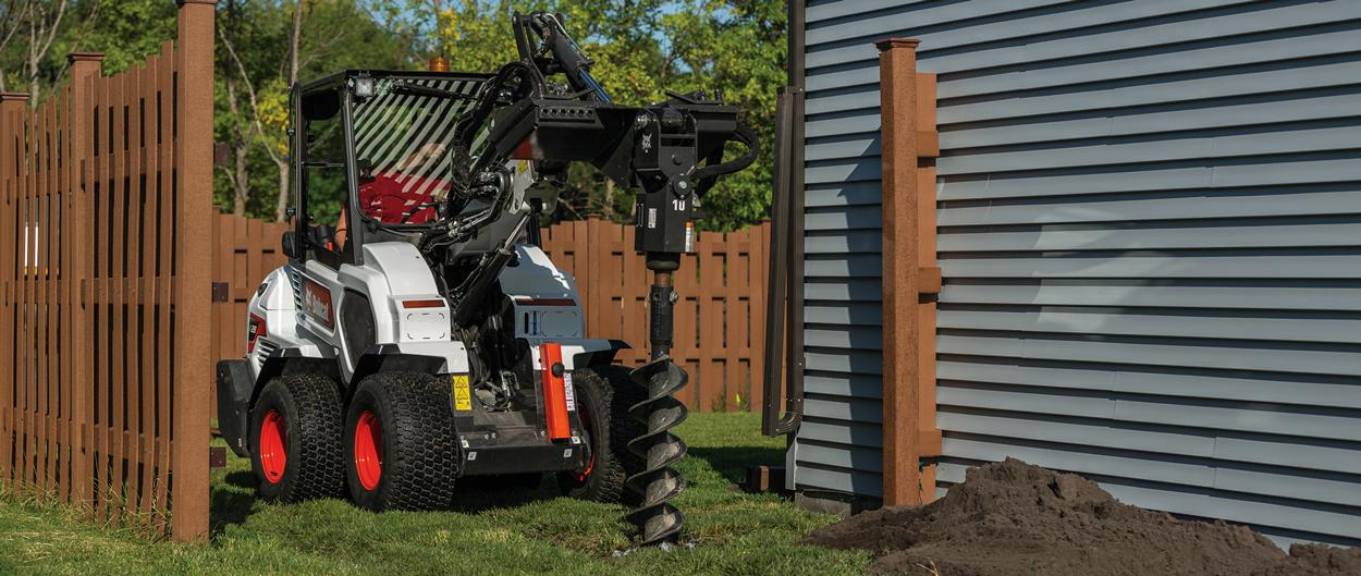 Bobcat L28 Small Articulated Loader Digging Fence Posts With an Auger Attachment