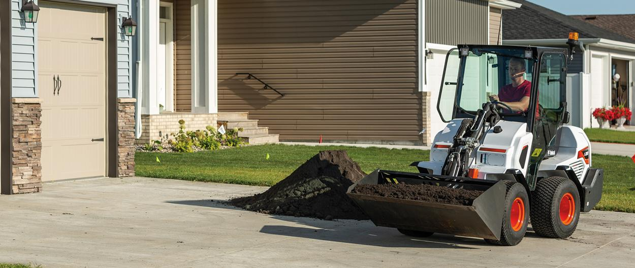 Bobcat L28 Small Articulated Loader With Bucket Carrying Dirt From a Driveway