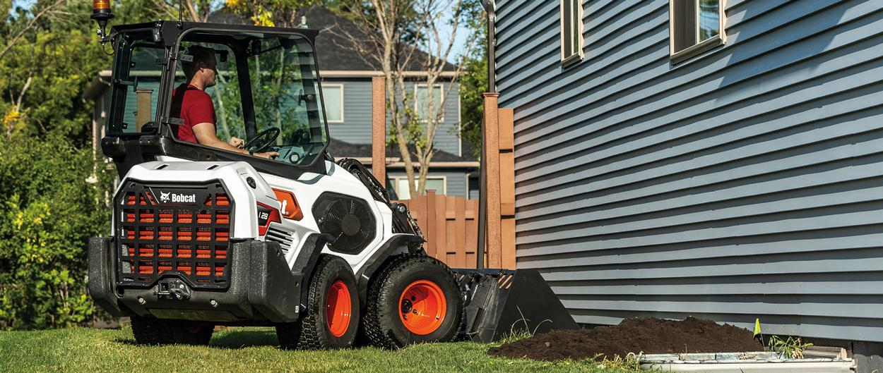 Small Articulated Loader Operator Maneuvers a Load