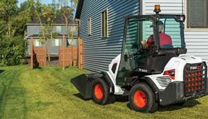 Landscaper Using Bobcat Small Articulated Loader To Move Rock