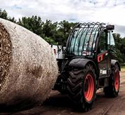 Bobcat VersaHANDLER using an attachment to move a bale of hay.