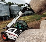 Bobcat VersaHANDLER telescopic tool carrier fully extended with a hay bale.