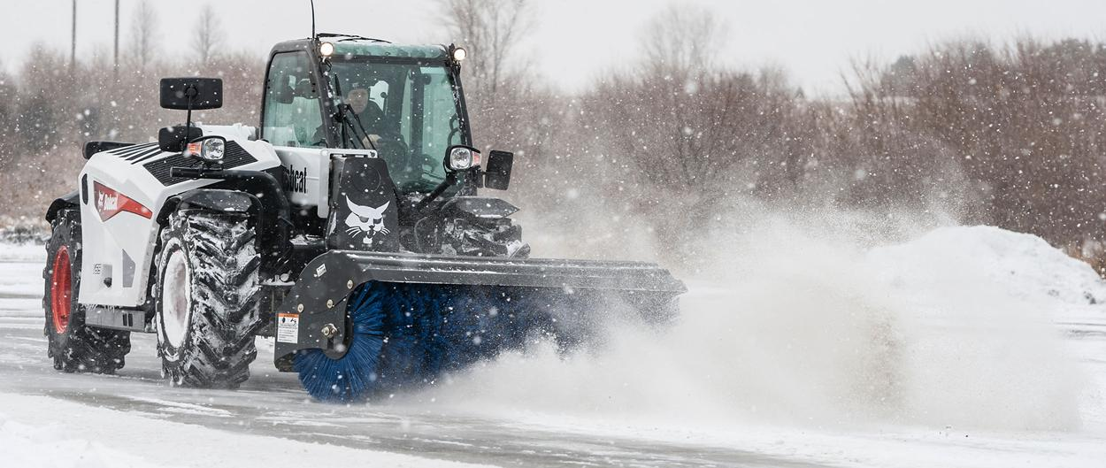 Bobcat V519 VersaHANDLER with angle broom attachment clearing snow.