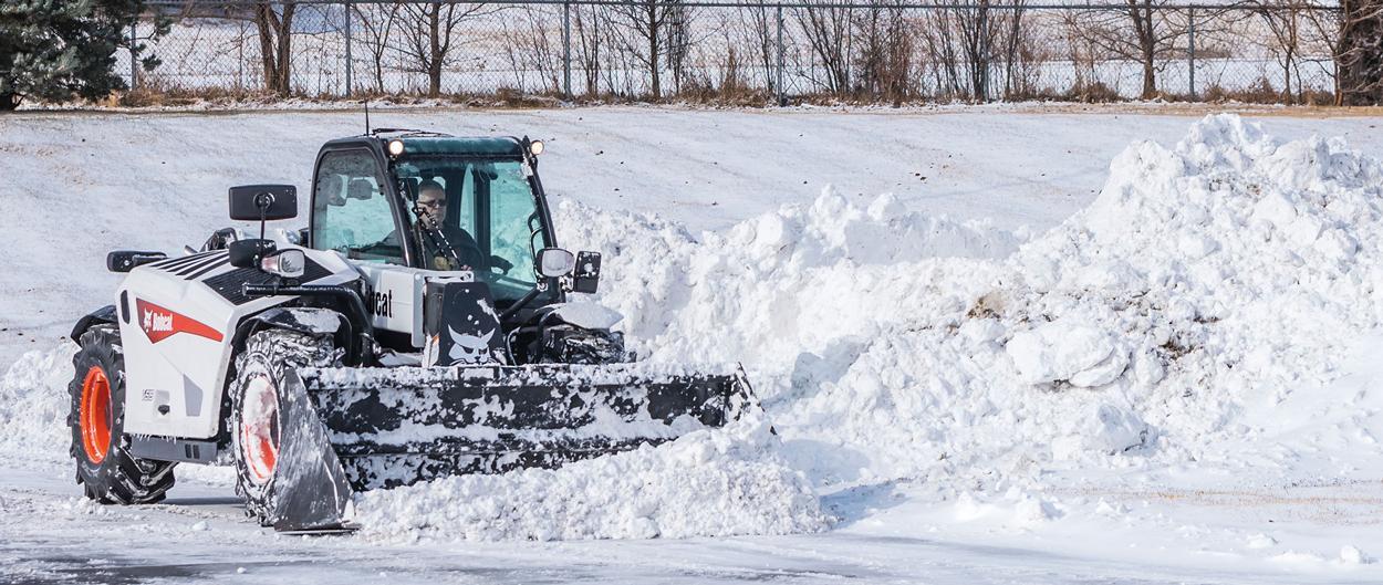 Bobcat V519 VersaHANDLER clearing a snowy lot.