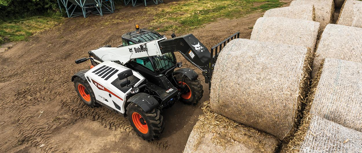 Bobcat V723 VersaHANDLER telescopic tool carrier (telehandler) and bale fork attachment lifting a round hay bale.