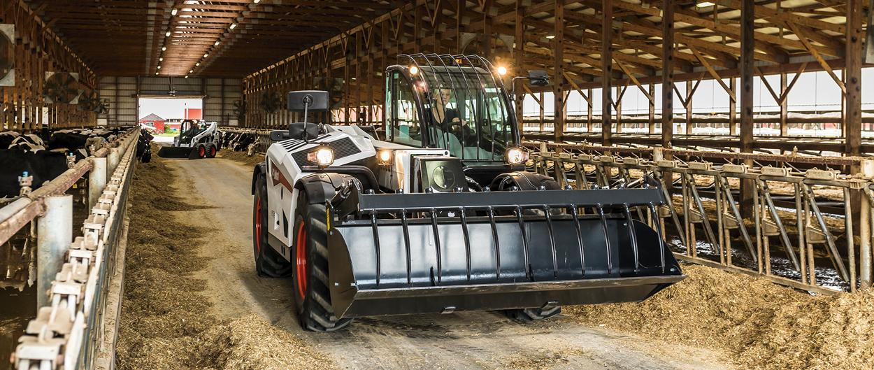 Bobcat V723 VersaHANDLER telescopic tool carrier (telehandler) with forklift attachment lifting large hay bales.