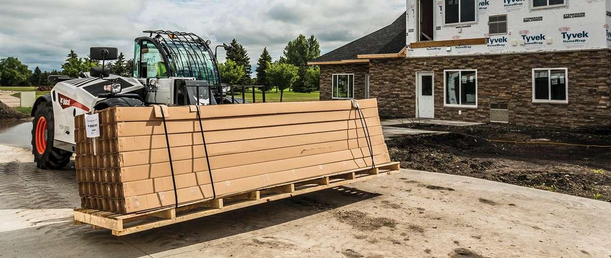 A Bobcat Telehandler Moves a Pallet of Lumber Across a Jobsite