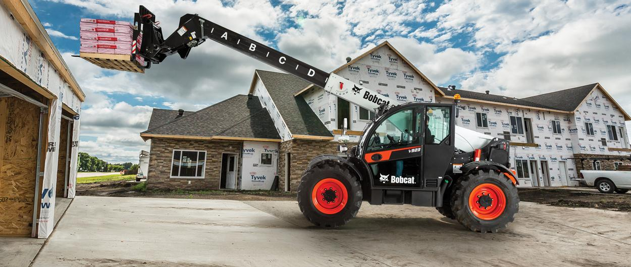 Bobcat V923 Telehandler With Pallet Fork Attachment Lifting Materials Onto A Roof At A Residential Construction Site.