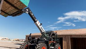 Bobcat V529 Telehandler With Pallet Fork Attachment Lifts Pallet Of Wood