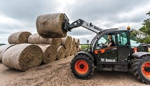 Bobcat V723 Telehandler With Round Bale Fork Attachment Lifts Bale Of Hay Onto A Stack