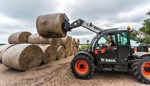Bobcat V723 Telehandler With Bale Fork Attachment Lifts Round Hay Bale Onto A Stack