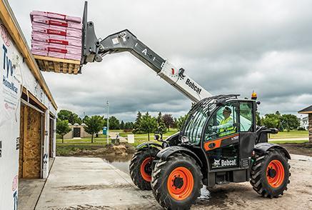 Bobcat V723 VersaHANDLER telescopic tool carrier (telehandler) lifting a pallet of materials.