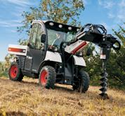 An auger mounted on the Toolcat 5600 is used to dig a tree hole.