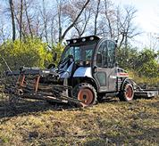 A utility grapple and 3 pt. rotary cutter work together to clear brush in a wooded area.