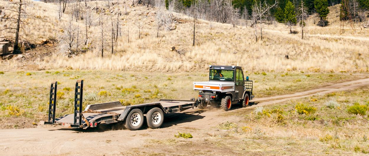Toolcat 5610 work machine pulling a dual-axle trailer on a dirt road.