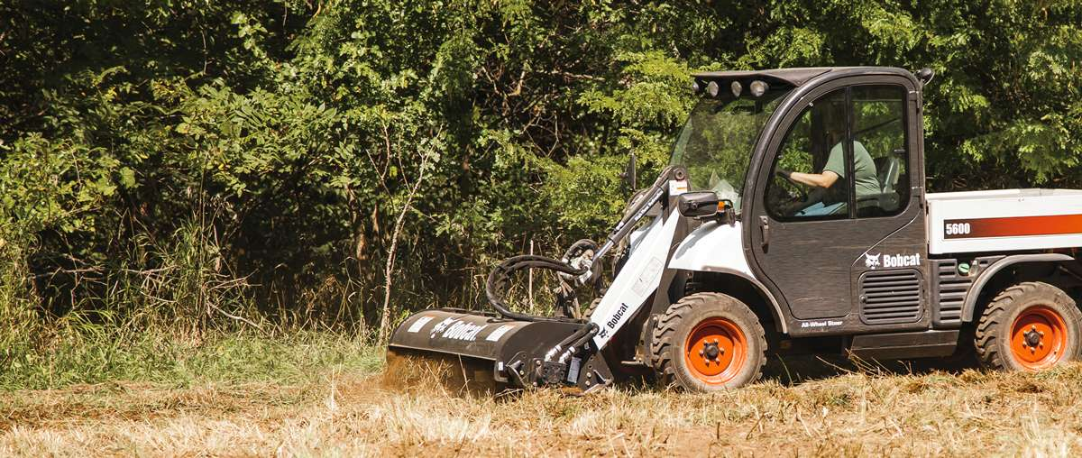 A Toolcat Utility Work Machine Works the Soil with a Tiller Attachment