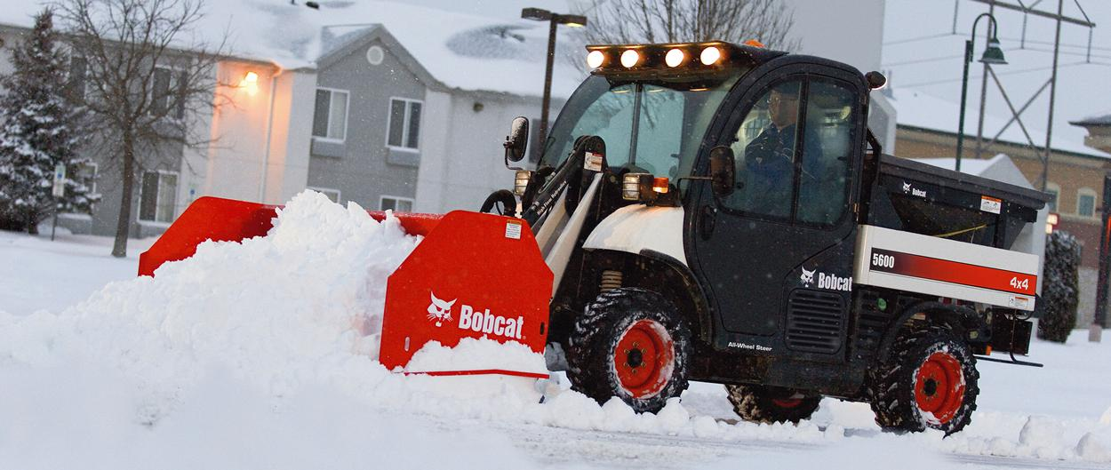 Toolcat 5600 with a snow pusher attachment clearing snow.