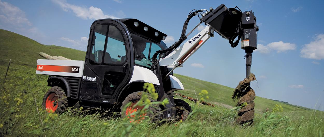 Bobcat Toolcat 5600 and auger attachment drilling holes in a field