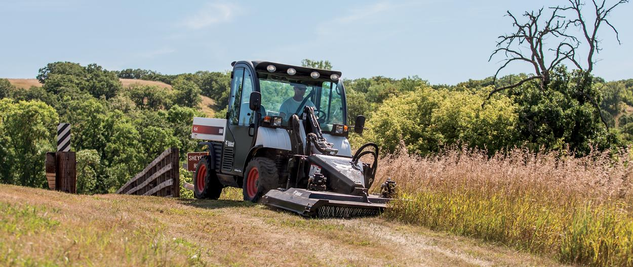 Bobcat Toolcat 5600 utility work machine and Brushcat rotary cutter attachment clearing away brush