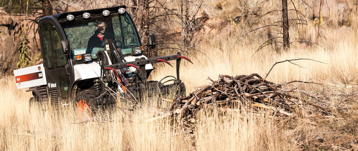 A Toolcat 5600 and utility grapple transport brush and twigs.