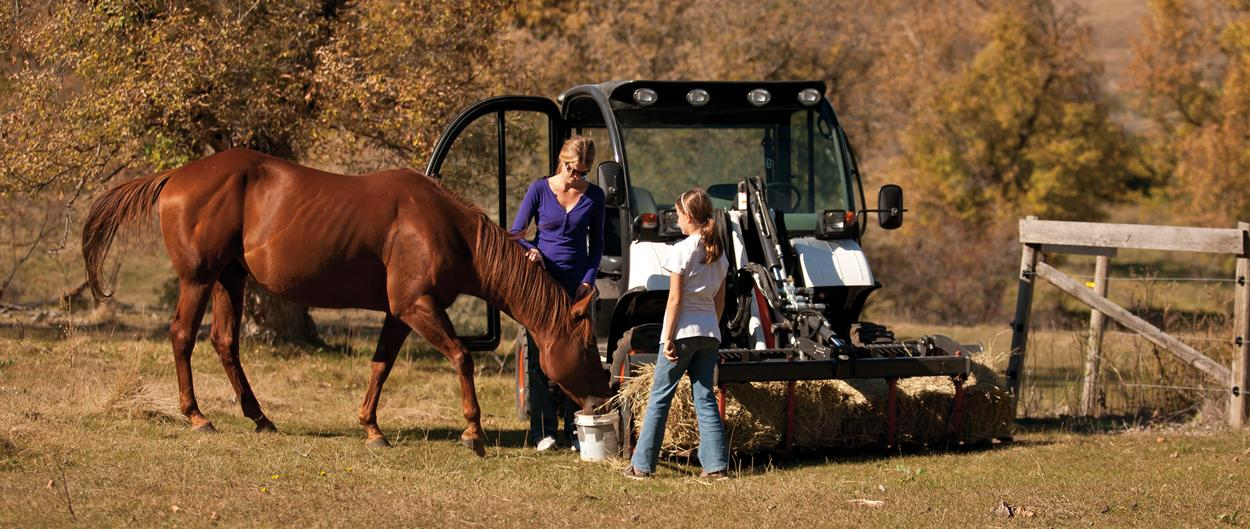 Mother and daughter use a Toolcat 5610 to carry feed to a horse on a hobby farm.