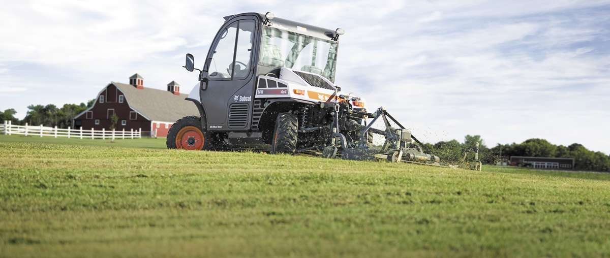 A Toolcat 5610 with a 3pt. mower implement mows a large grassy area on a hobby farm.