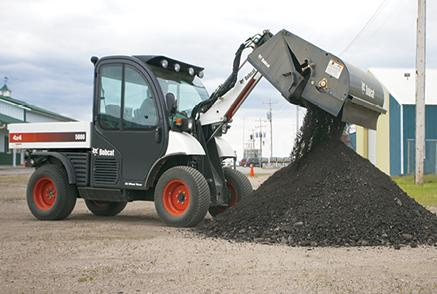 Toolcat 5600 utility work machine dumping out a sweeper attachment.