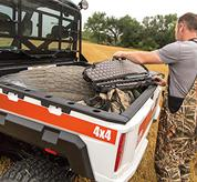 A hunter loads a gun case and decoys into the cargo box of a Bobcat 3400 utility vehicle.