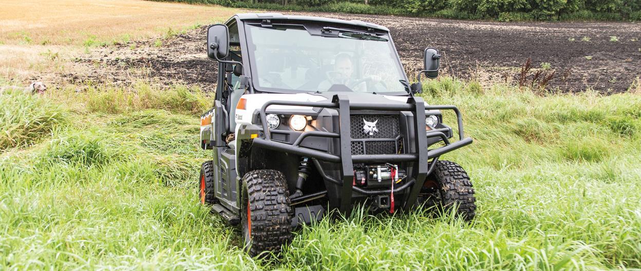 Bobcat 3400 utility vehicle travels up a grassy trail near a field.