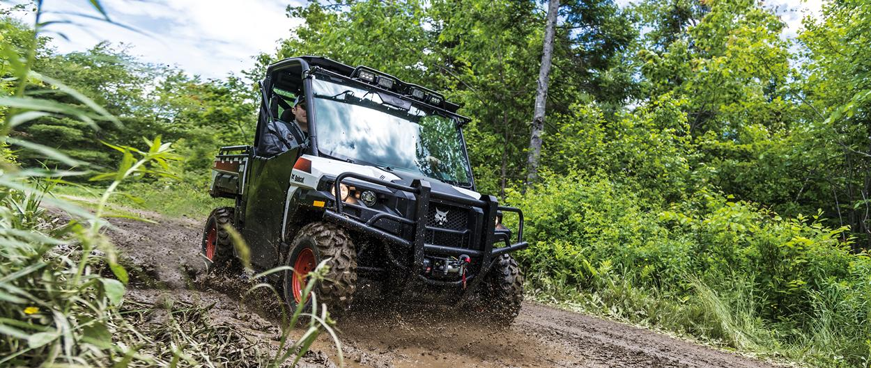 A Bobcat 3400 utility vehicle (UTV) moving through a muddy trail.