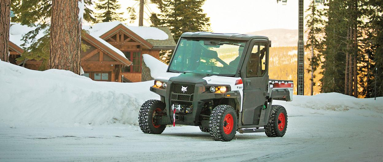 A Bobcat 3600 utility vehicle drives on a snowy mountain road.