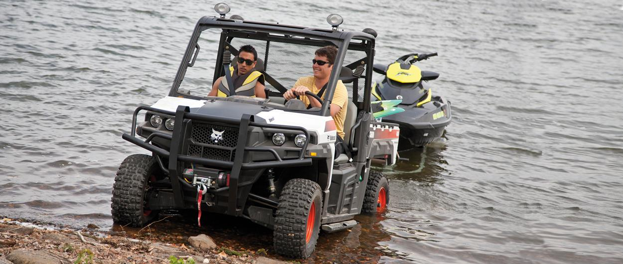 Bobcat 3600 utility vehicle pulling a trailer jet ski out of a lake.